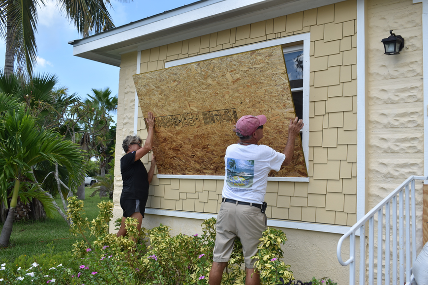 Karen and Brian Feeney board up their front window before evacuating Longboat Key.