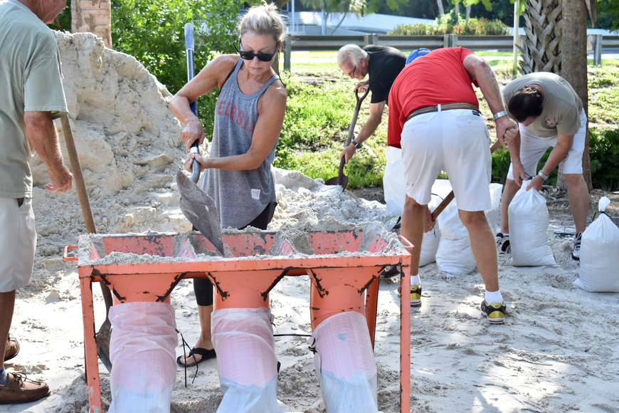 Lindsey Brown shovels sand into a bag at the Broadway Street beach access.