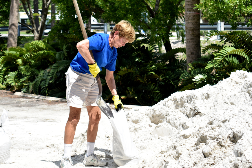 Linda Aitkin shovels sand into a bag to prepare for Hurricane Irma.