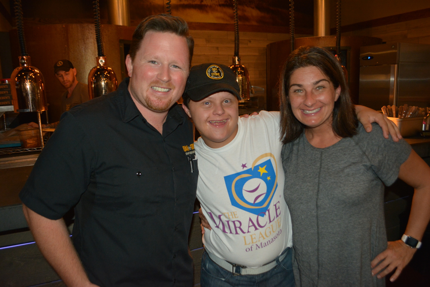 Oak & Stone Assistant General Manager Patrick Goeser visits with The Miracle League's Andrew Leibin and his mom, Jaycie.