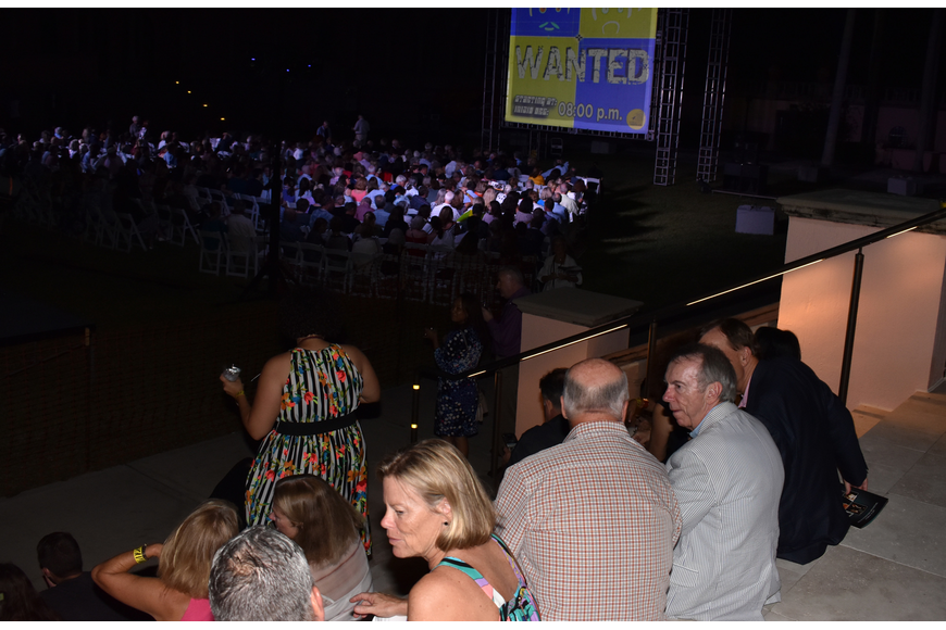 "Guests sat on the lawn and on the stairs for the performance of ""WANTED"" by eVenti Verticali at First Night RIAF 2017 on Oct. 18 at The Ringling."