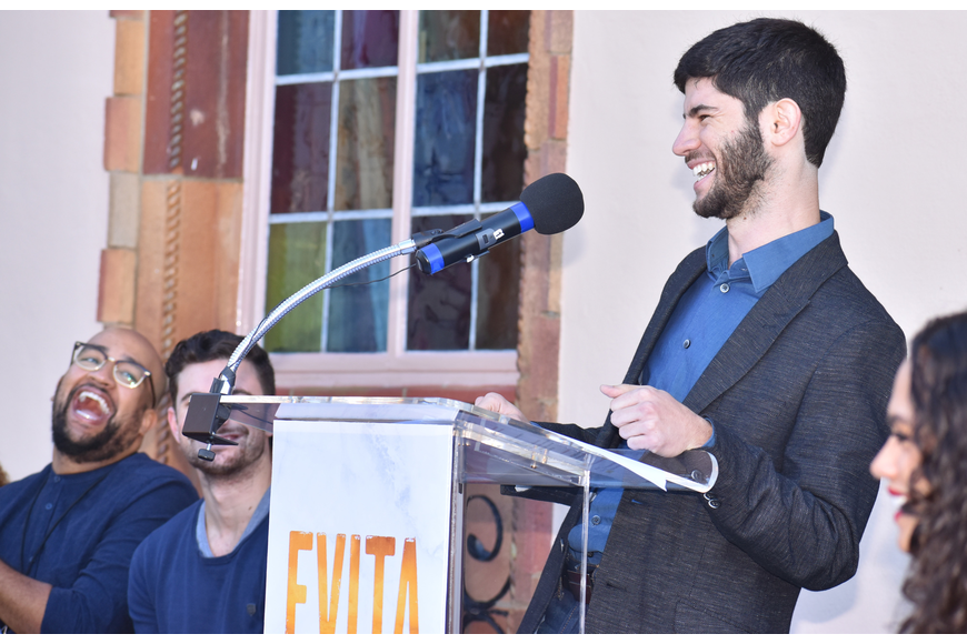 "Music Director Sinai Tabak laughs while addressing the crowd about his experience with ""Evita."""