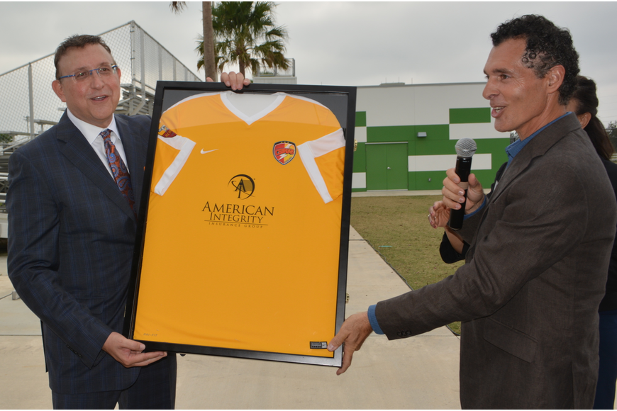 Bob Ritchie, the president and CEO of American Integrity Insurance, accepts a Chargers jersey with his company logo on it from Premier Sports Director Antonio Saviano.