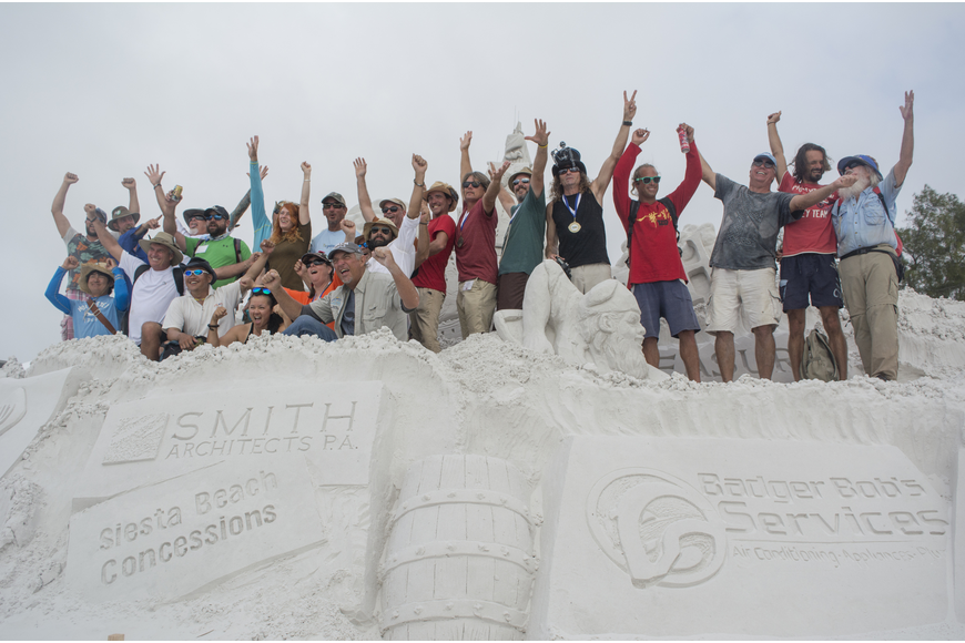 Crystal Classic International Sand Sculpting Festival sculptors pose for a photo near the entrance of the festival.