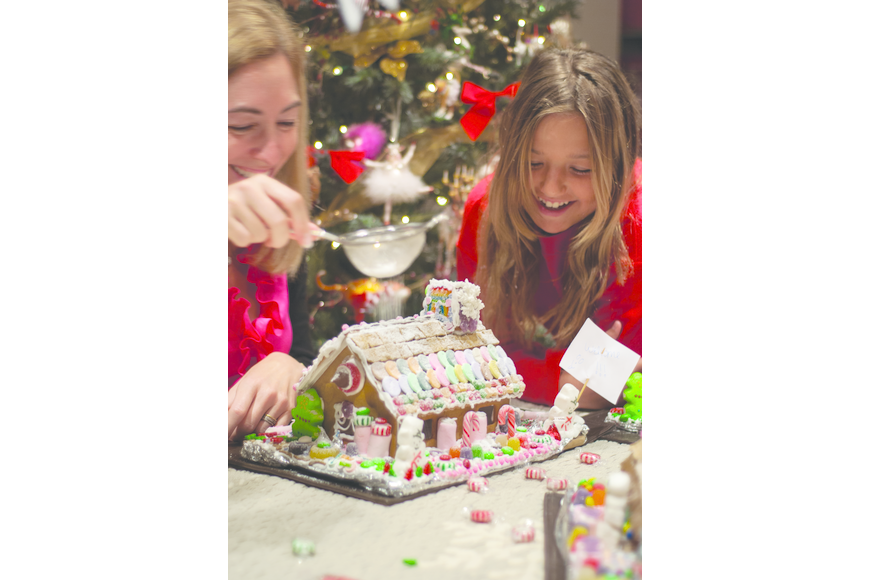 Julie Deffense and her niece Madalena Deffense decorate a gingerbread house.