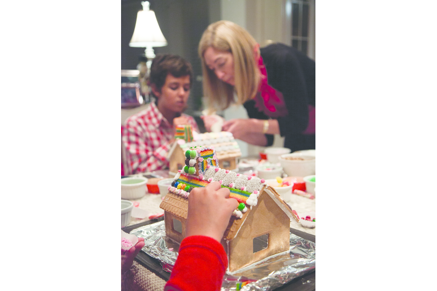 Julie Deffense helps her nephew Lawrence Deffense decorate a gingerbread house. Courtesy photo.