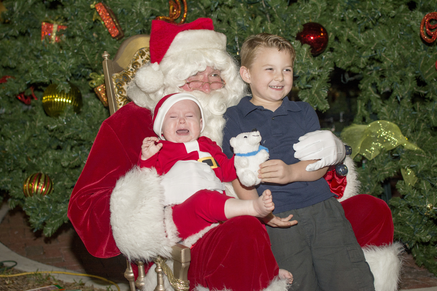 Kye and Silas Daughtrey pose with Santa at the downtown tree lighting celebration.