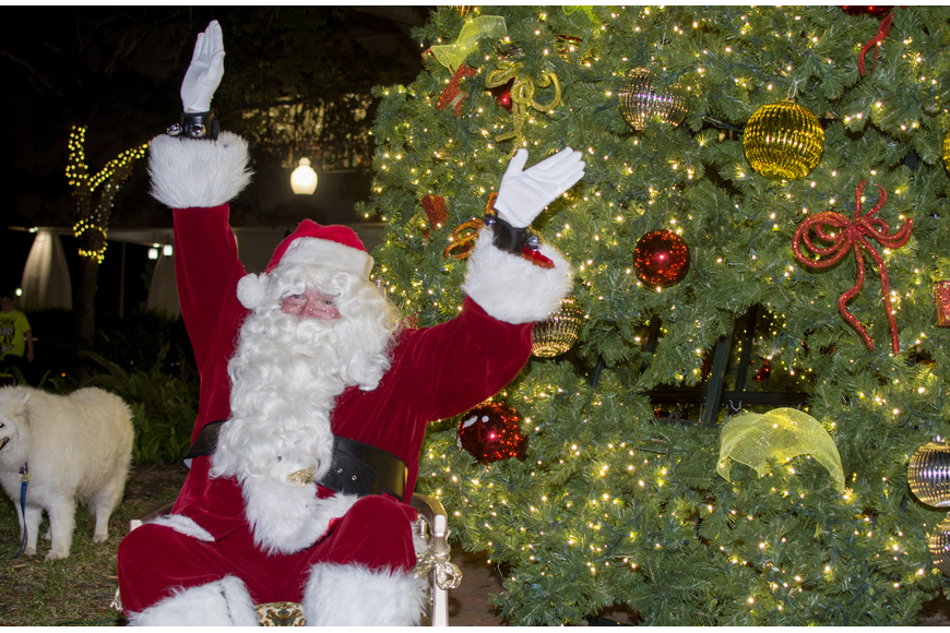 Santa celebrates after lighting the downtown holiday tree.