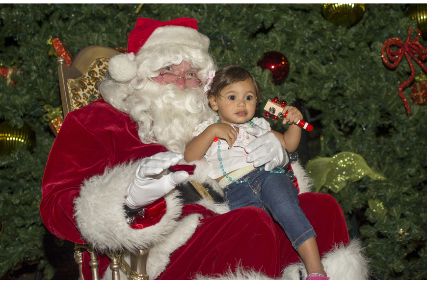 Sophia Rios poses with Santa Claus in front of the tree in Five Points Park.