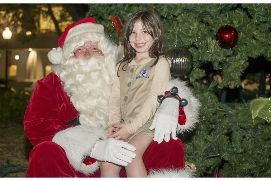 Daphne Silvestri poses with Santa Claus in front of the tree in Five Points Park.