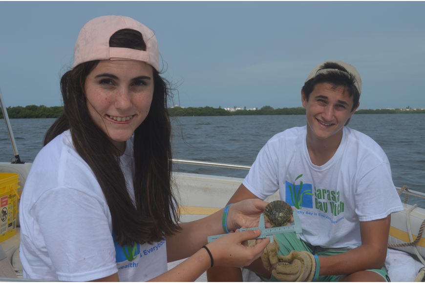 Ellie Martin, 14, measures a scallop with her brother, Jack.