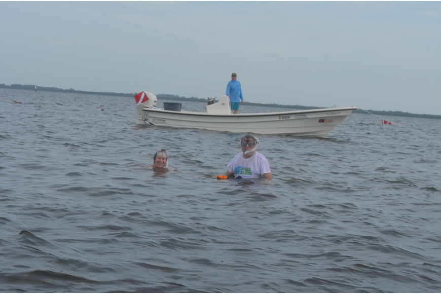Beth and Scott Brewer search for scallops from Steve Traves' boat.