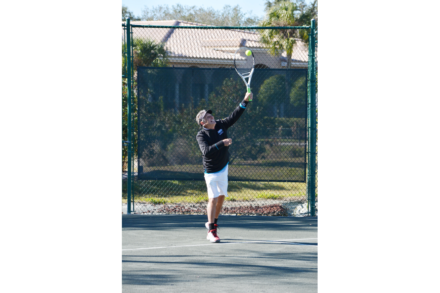 Enrique Vela serves up a point in the Division 2 mixed doubles match Sunday.