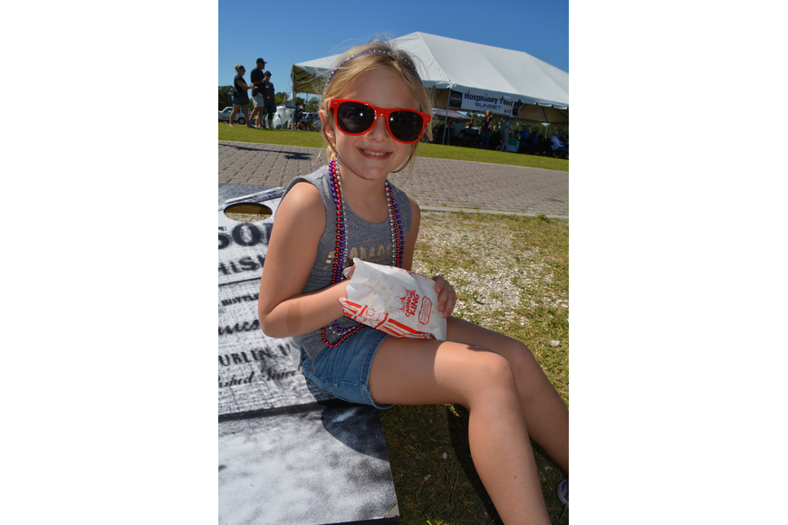 Sarasota's Marin Lank, 4, munches on popcorn from the Observer Media Group booth.