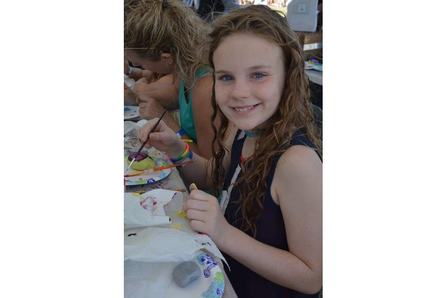 Nine-year-old Mia Hynes, of Sarasota, paints a peace sign on a rock at the Sarasota Rocks booth.