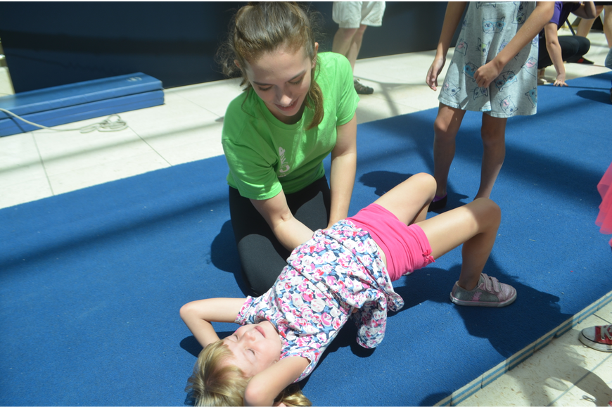 Sailor Circus Academy's Teresa Powell, 16,  helps Parrish's Riley Zawacki, 4, learn how to do a back bend,  a basic tumbling technique.