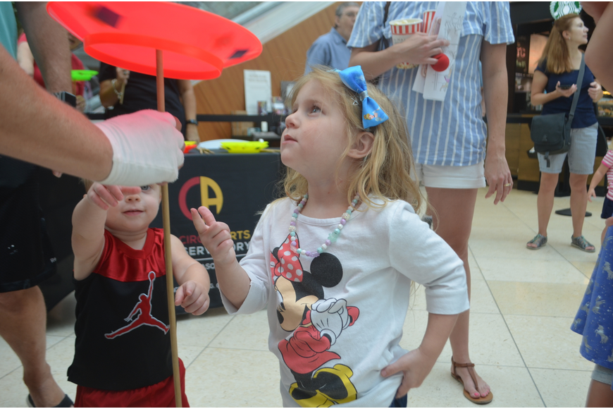 University Park's Harper Lassiter, 3, and her 1-year-old brother, Jackson, stares at the spinning plate.