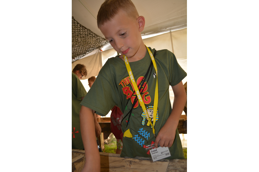 Lakeland's Creed Andersen, 7, digs for a snake in an air-conditioned tent.