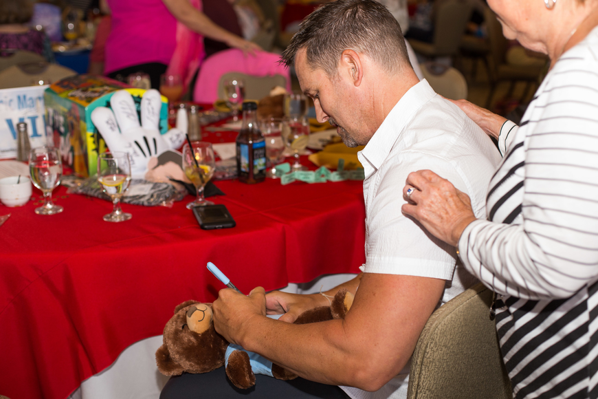 Eric Martsolf signs bears for guests.