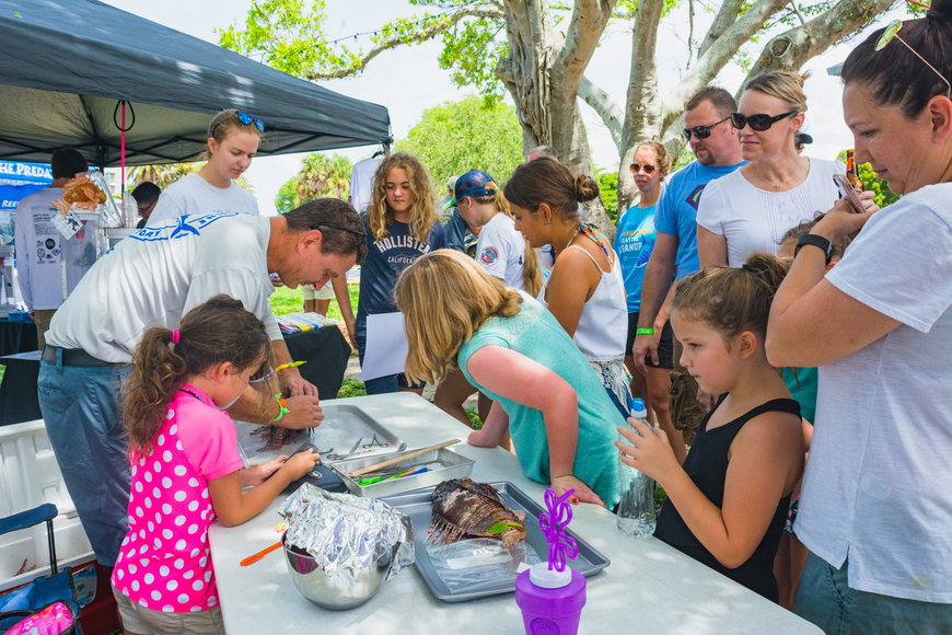 Attendees observe a lionfish dissection.