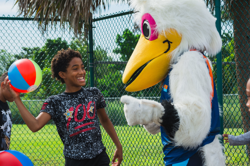 Jeremiah B. dances with Scully, the World Rowing Championship's pelican mascot.