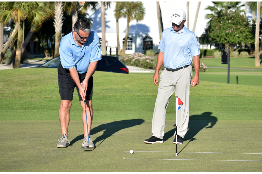 Longboat Key Club Director of Golf Terry O'Hara gives Longboat Key Fire Rescue Chief Paul Dezzi advice as he putts.