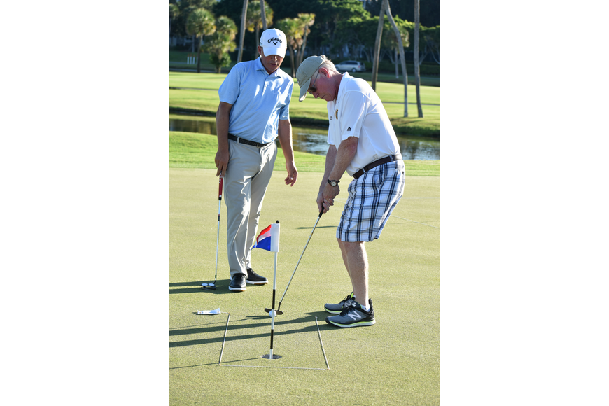 Longboat Key Club Director of Golf Terry O'Hara gives Commissioner Ken Schneier advice as he putts.