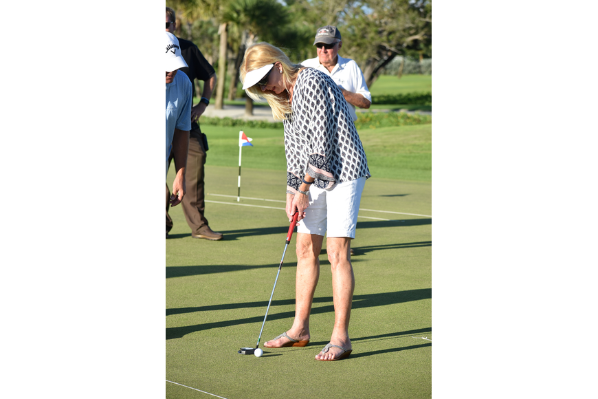Assistant to the Town Manager Susan Phillips taps the ball into the hole.