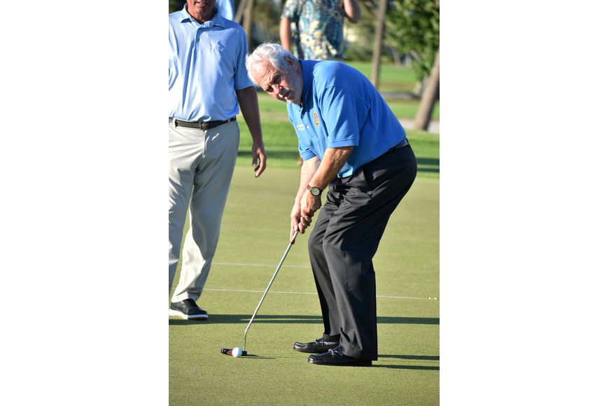 Commissioner Irwin Pastor takes his turn at the putting challenge.