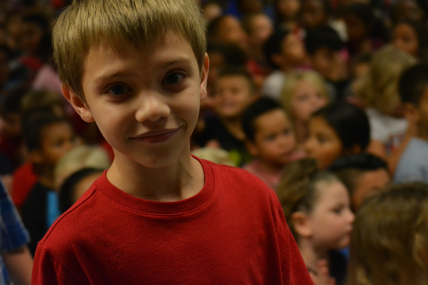 Peyton Painter is all smiles as he and other fourth-graders pile on to the stage.