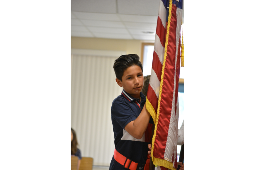 Fifth-grader Aurelius Pena presents the colors to lead off the presentation.