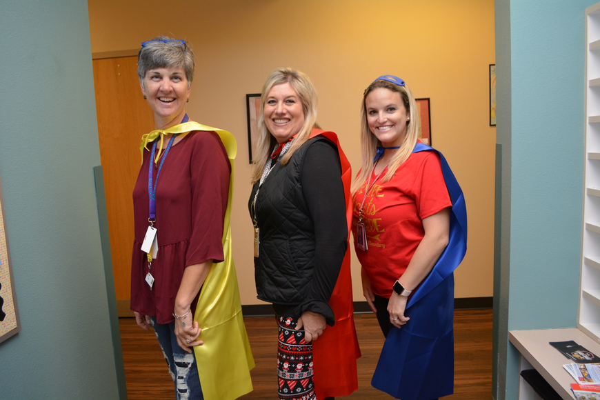 McNeal Elementary substitute Skoula Clark and second-grade teachers Angie Hughes and Jodi Samson love their capes.