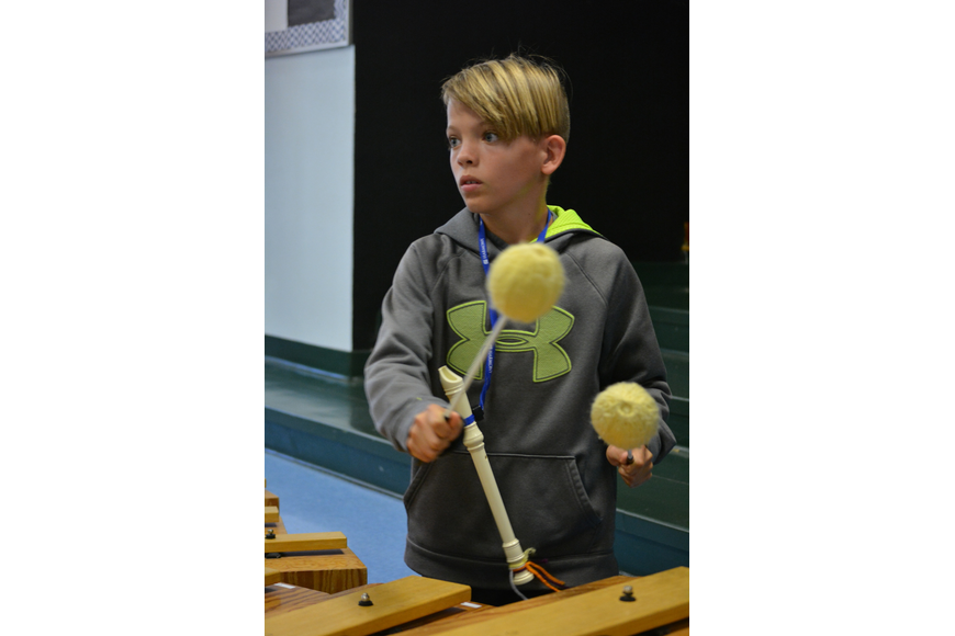 Cooper Flammang drums during a song about Sneezy, the Snowman.
