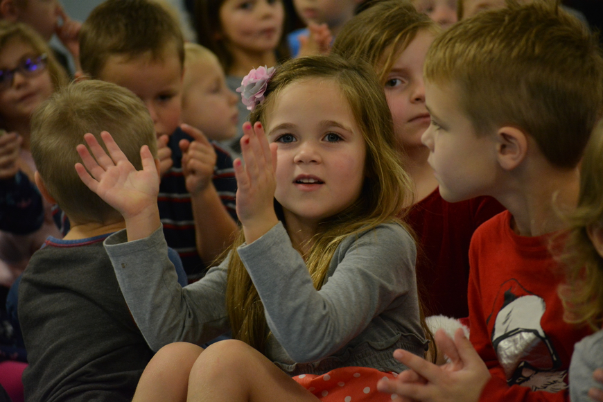 Pre-kindergartner Grace Foley, next to Carson Macek, is all smiles as kindergartners sing bout a snowman.