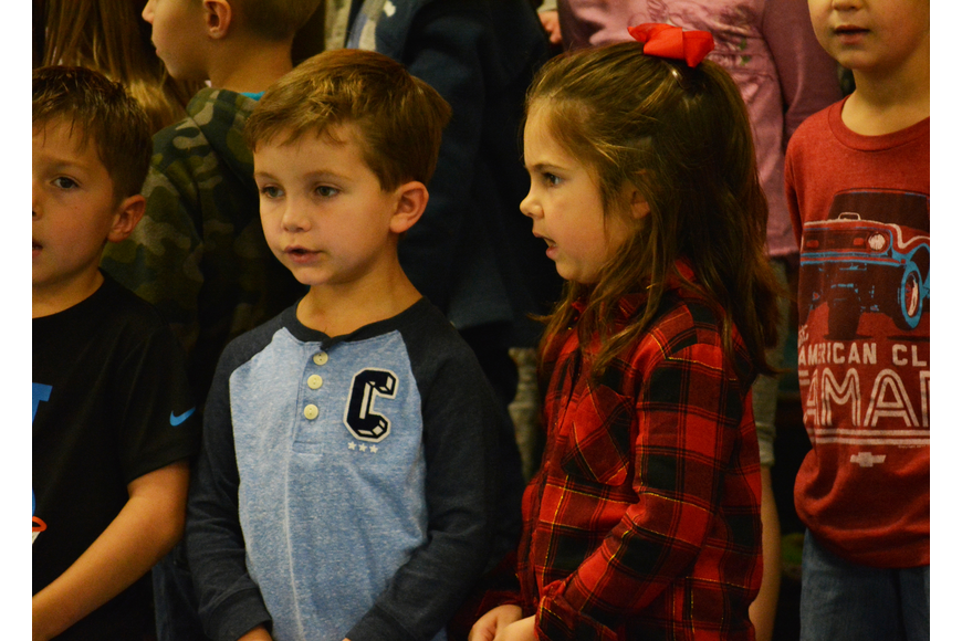 Kindergartners Grayson Rist and Nora Blasewitz have fun singing about Sneezy, who can never seem to get warm enough.