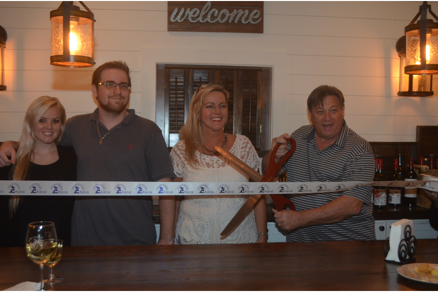 Kasey Gamble, Cole Gamble and co-owners Darlene Gamble and Stu Gamble cut the ribbon to the Siesta Key Wine Bar.