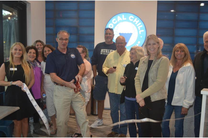 Bob Davidson, cutting the ribbon, owns Local Chill, with Suzanne Munroe (in the tan jacket)'s husband, Rick Munroe, not pictured, and John Davidson, not pictured.