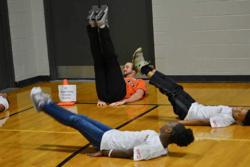 Orioles pitcher Mike Wright Jr. performs leg lifts with students.