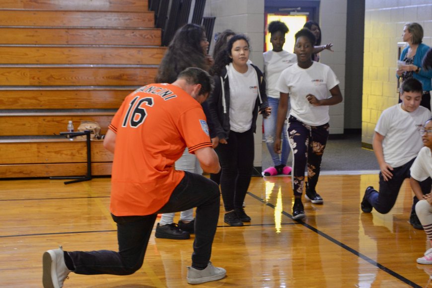 Orioles outfielder Trey Mancini performs lunges with students.