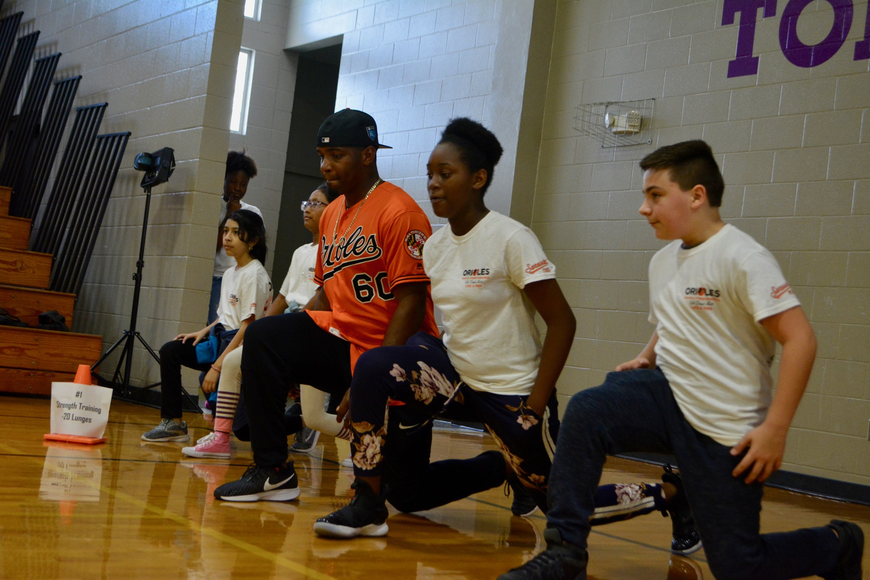 Mychal Givens does lunges with students.