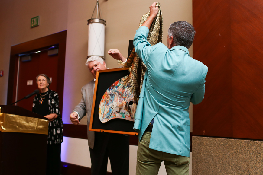 Eric Bowyer and Peter Imrik pull back the sheet to reveal the stolen painting being returned.