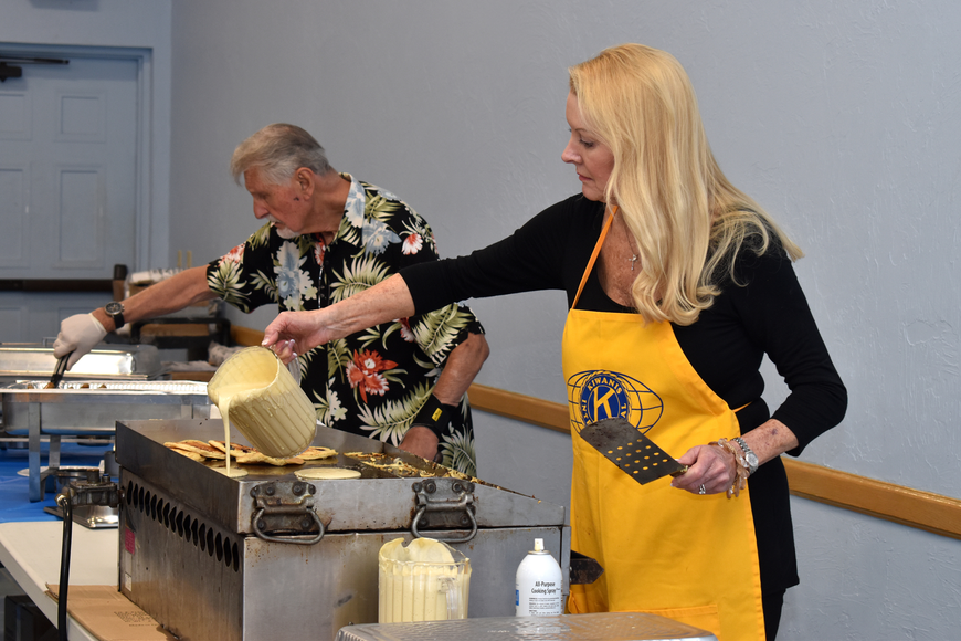 Ed Krepela and Susan Phillips make pancakes and serve sausage to guests.