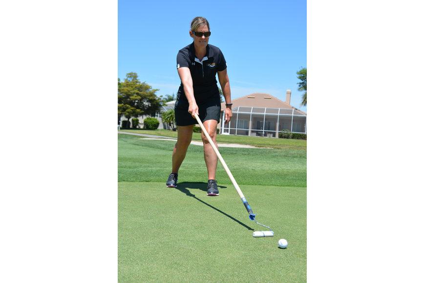 Shelly McAvoy, of sponsor Cooper Creek Dental, has the lead on the longest putt using a paint roller.