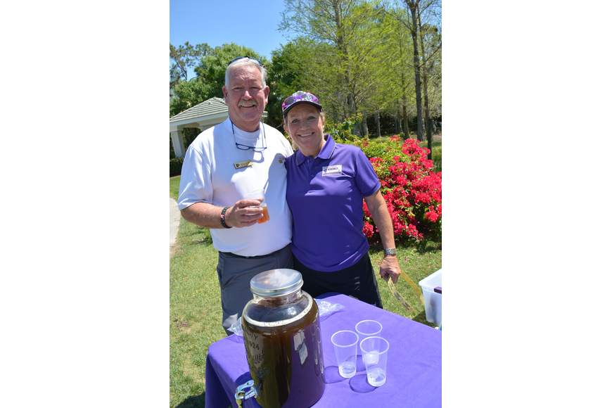 Rosedale Golf and Country Club golf course superintendent Doug Cunefare tries some of the peach whiskey iced tea provided by sponsor Dee Donegan, of Designed Finishes LLC. Donegan is Rosedale's women's golf champion.