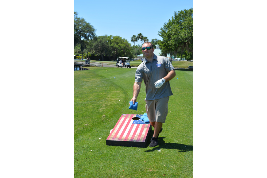 Ellenton's Timothy Ball tries his hand at corn hole at Hole 10, where Veterans Air was a sponsor.
