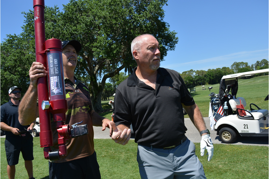 Jeff Ball opts for shooting his ball with an air gun rather than hitting it on a special Hole 10 challenge. Air Golf Pro Launcher Team Challenger owner Robert Block, left, watches.