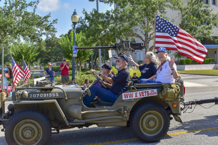 World War II veterans smile and wave to the crowd while riding down Main Street.