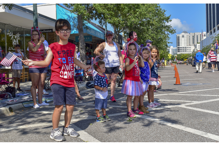 Children decked out in red, white and blue watch the parade as it goes by.