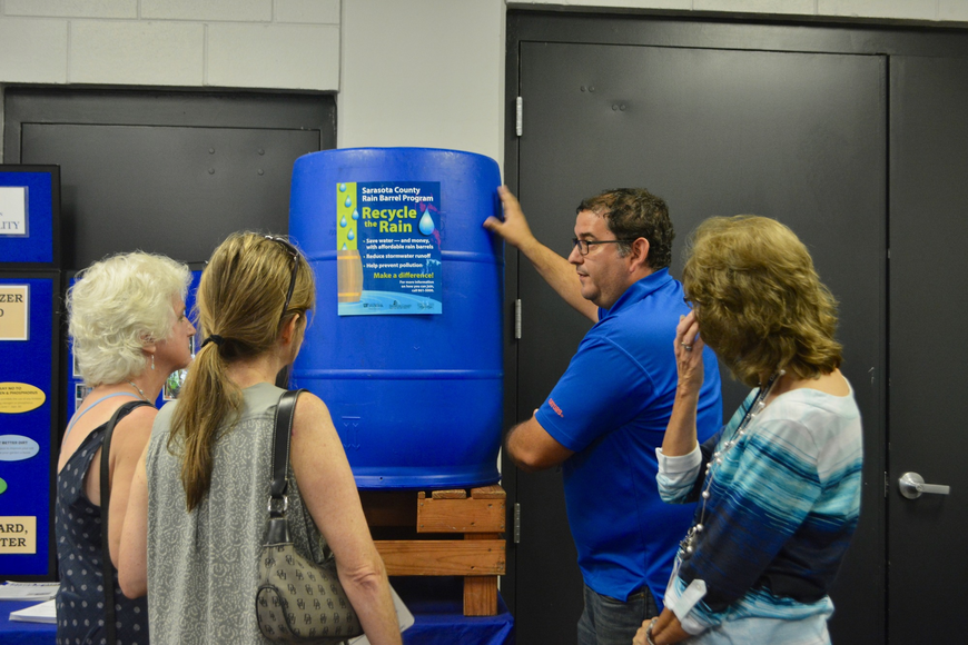 David Puoso, who works for the county's air and water quality department, shows attendees how a rain barrel works