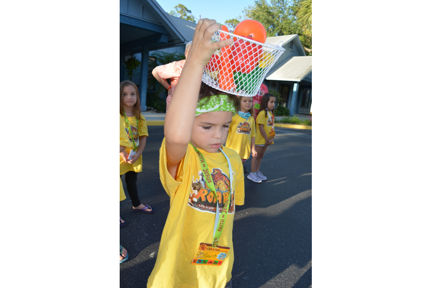 Six-year-old Grant Pecora tries to balance a bucket of fruit on his head.